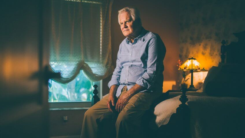 Depressed senior man alone sitting on bed edge with dozens of pill container at his feet.