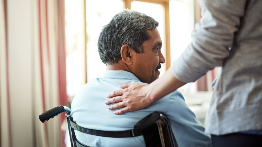 Shot of a young nurse caring for a senior man in a retirement home.