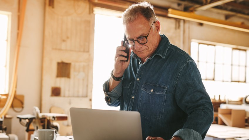 Senior man talking on cell phone and using laptop on work table.