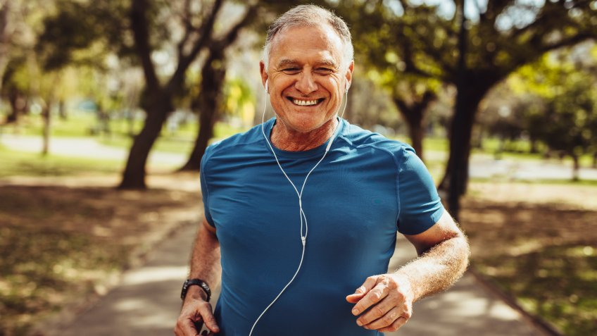 Portrait of a senior man in fitness wear running in a park.