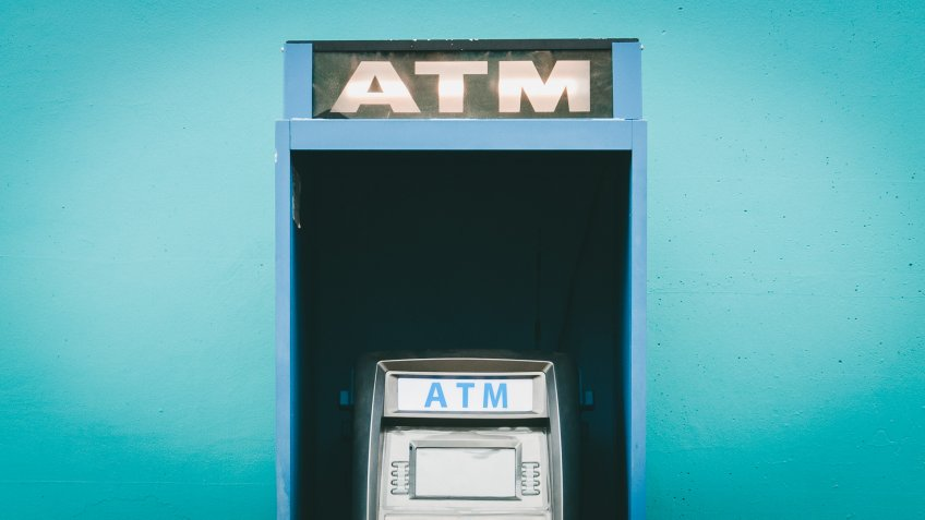 blue public ATM, Automated Teller Machine on street in front of wall.