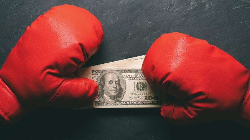 Boxing Gloves holds the dollar banknote on black cement background.