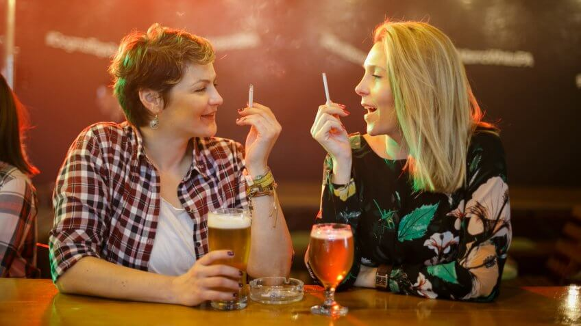 Two mid adult women having beer at the bar counter, talking and smoking cigarettes.