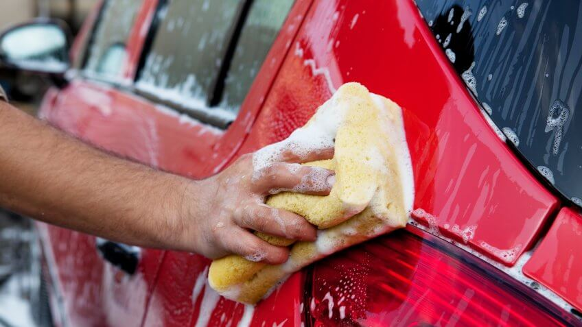 washing a red car with yellow sponge.