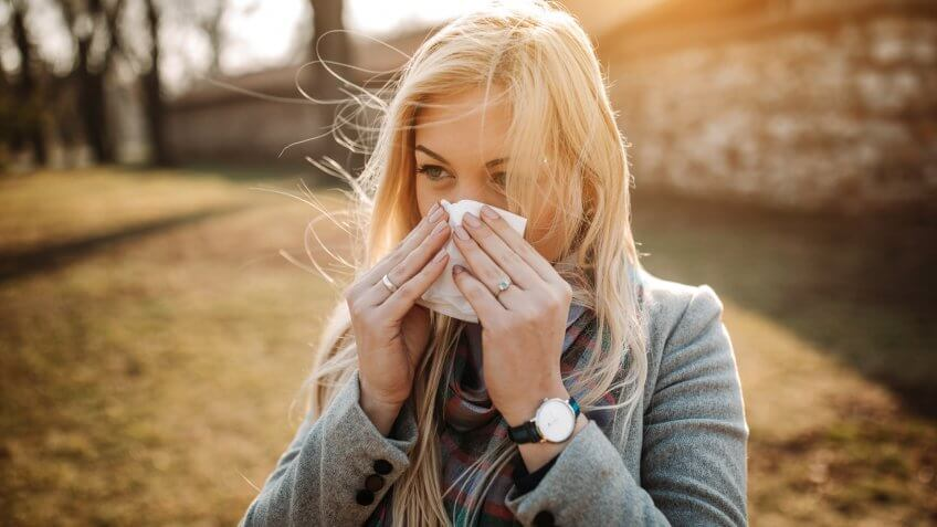 Sick blonde blowing her nose.