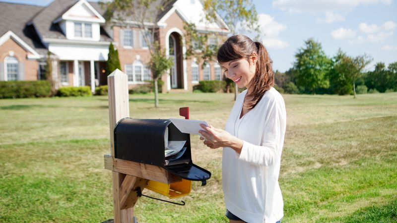 Beautiful american housewife checking mail box.