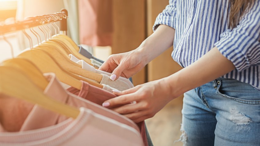 Unrecognizable woman choosing clothes on rack in showroom.