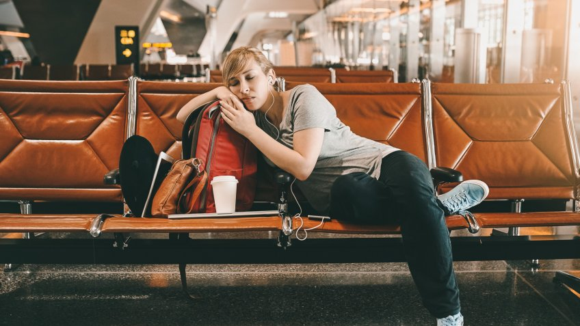 Full length shot of an attractive young woman sleeping in an airport.