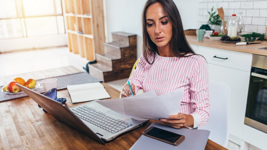 Woman working with documents and laptop in the kitchen at home.