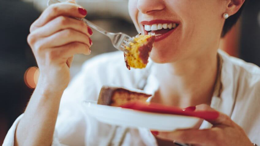 Smiling young woman is enjoying a piece of lemon cake.
