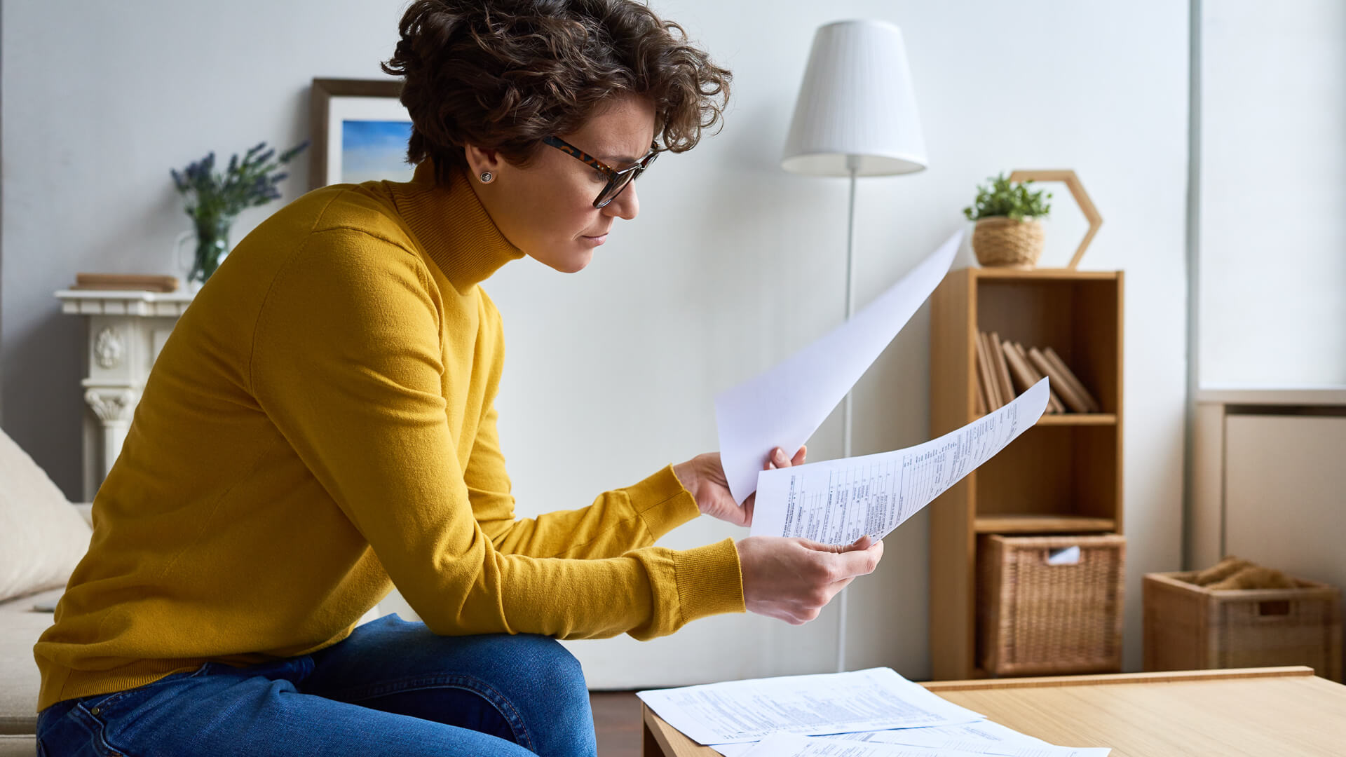 Concentrated woman reviewing financial documents at home.