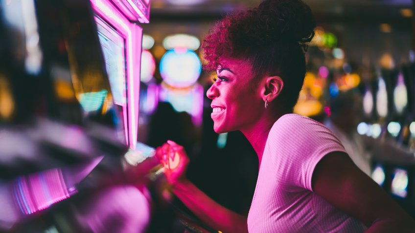 woman having fun playing slot machine at casino pulling lever.