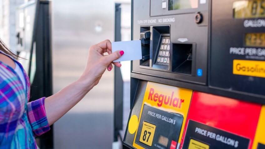 Female hand inserting credit card into petrol machine.
