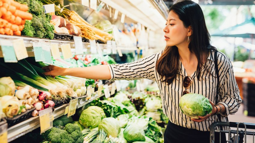 asian local woman buy vegetables and fruits in supermarket.