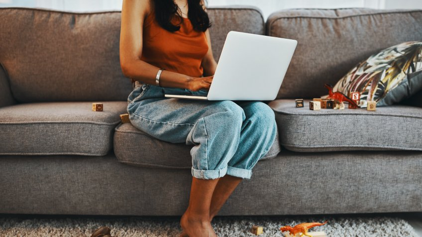 Cropped shot of a woman using a laptop on the sofa surrounded by toys at home.