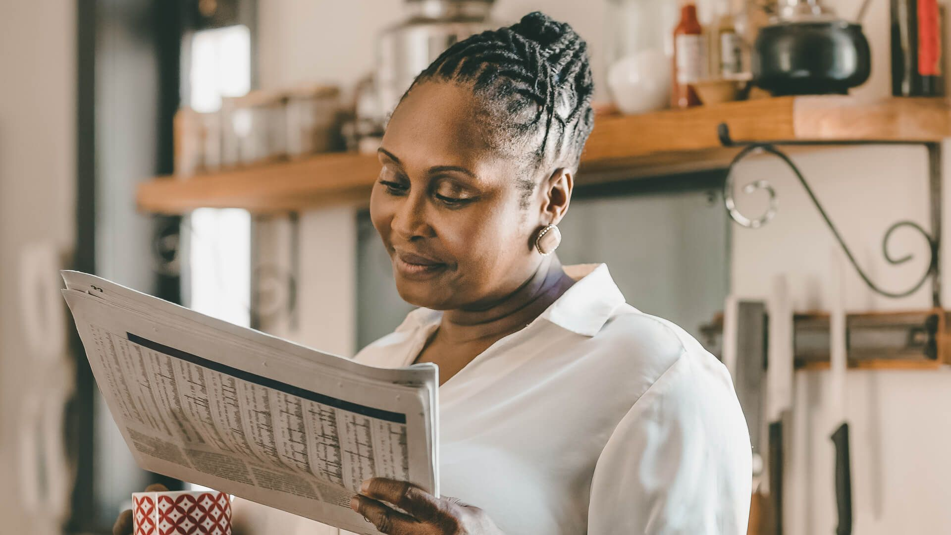 Smiling African American woman drinking a cup of coffee and reading the newspaper while standing in her kitchen in the morning.