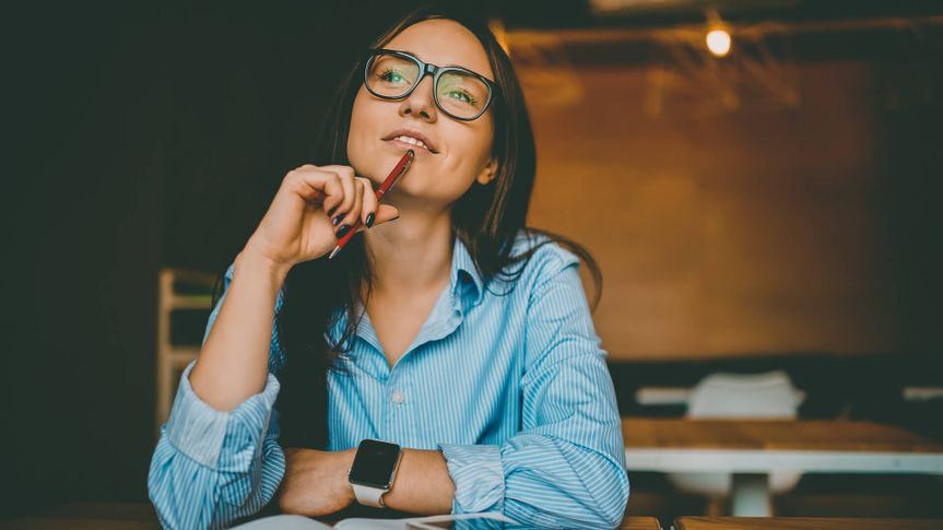 Dreamy woman podring while working on journalistic publication sitting with notebook in cafe,thoughtful female student in eyewear doing homework task solving problems and analyzing information.