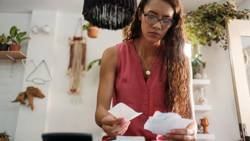 A young latin woman sitting, holding receipts and looking at them with a worried face.