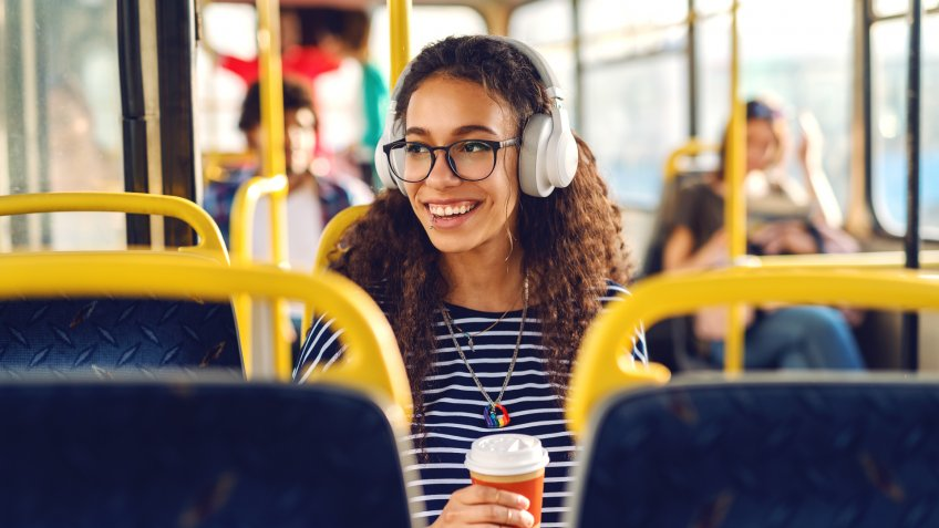 Girl sitting ina a bus drinking coffee, listening to music and looking trough window.
