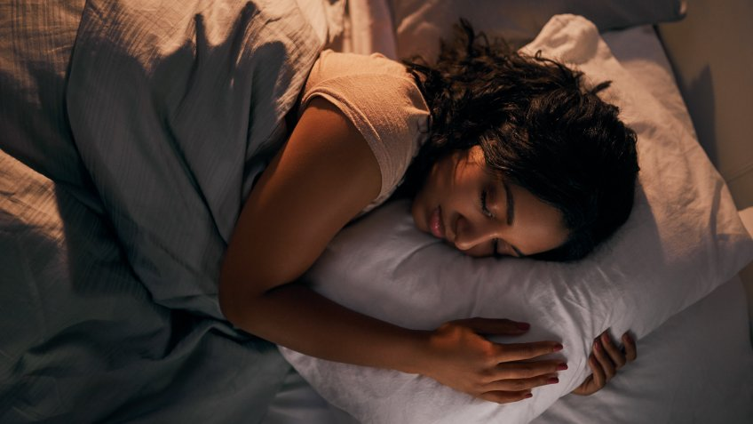 High angle shot of a beautiful young woman sleeping in her bed at home during the night.