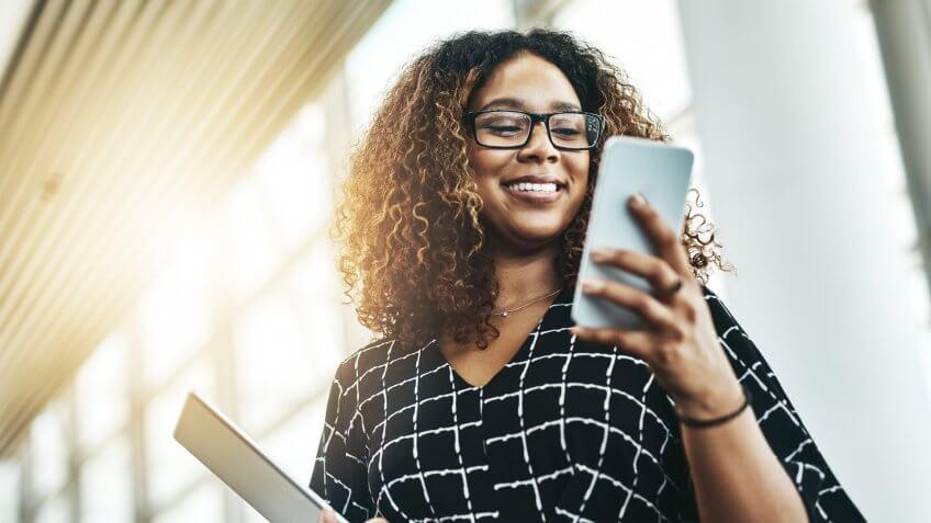 Low angle shot of an attractive young businesswoman using a smartphone in a modern office.