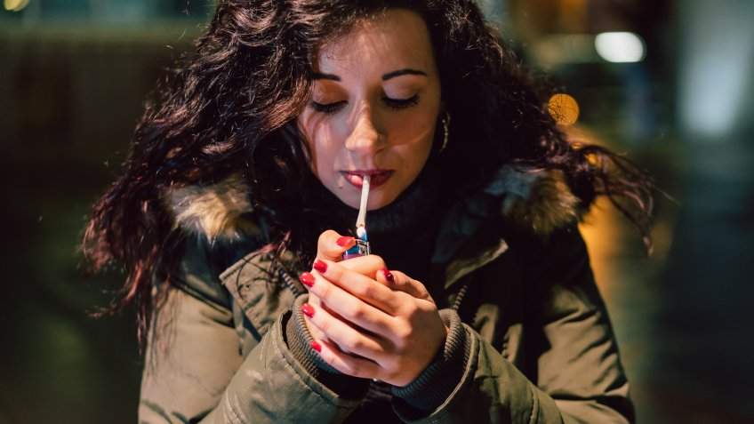 Young Adult Woman Lighting Cigarette In The City At Night.