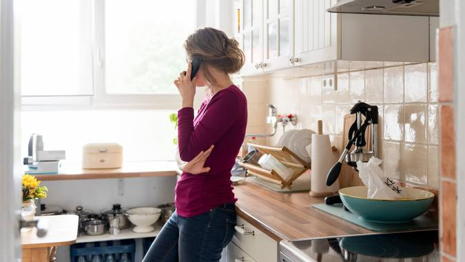 A young woman is at home in her apartment making a phone call.