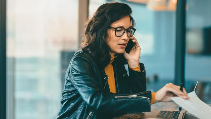 Asian business woman talking on cell phone while working at office.