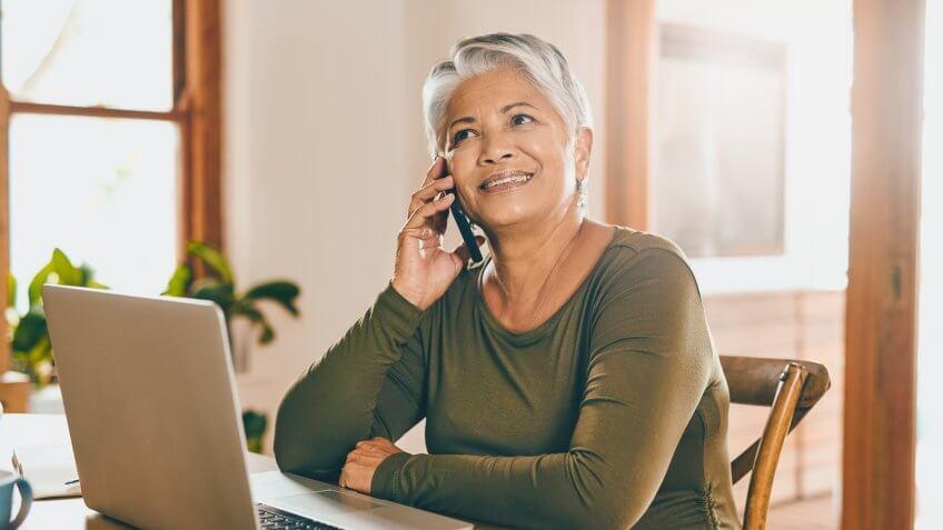 Shot of a mature woman talking on a cellphone while working on a laptop at home.