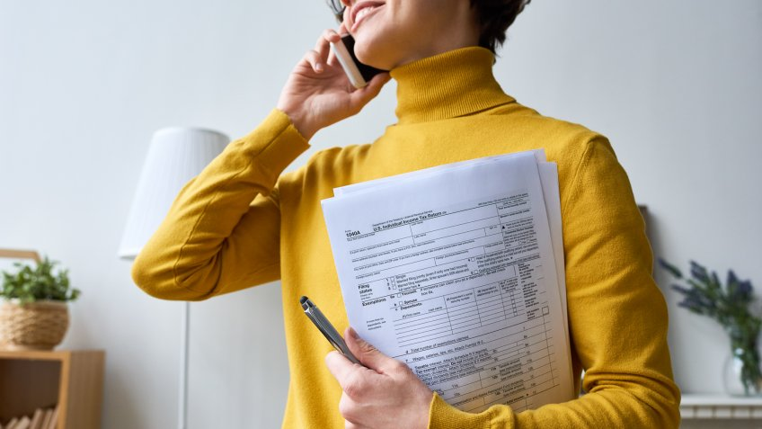 Close-up of positive young woman in glasses standing in living room and holding individual income tax return form while talking by mobile phone.