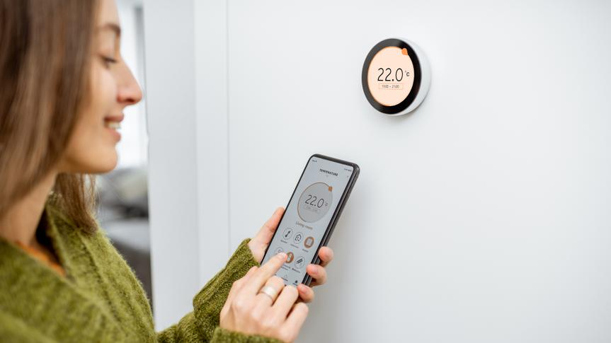 Woman dressed in green sweater regulating heating temperature with a modern wireless thermostat and smart phone at home.