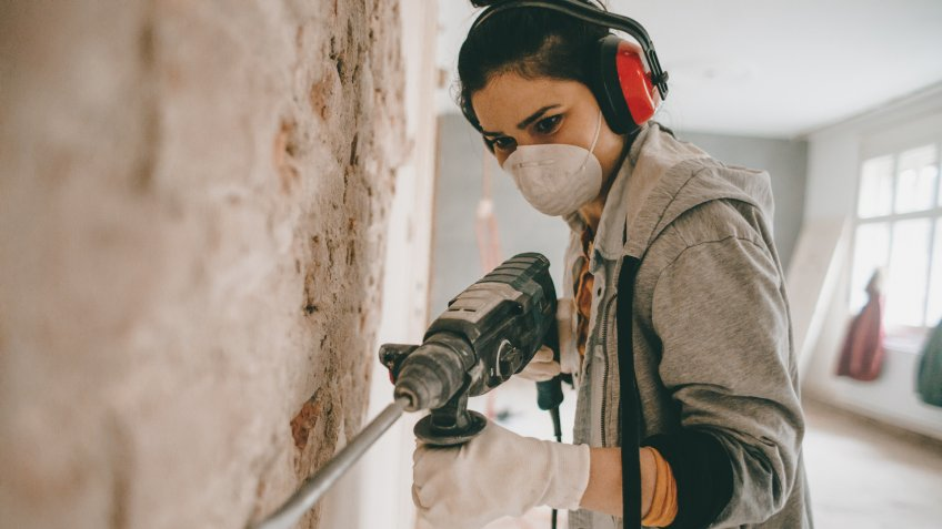 Young woman using drilling machine during reconstruction of her apartment.