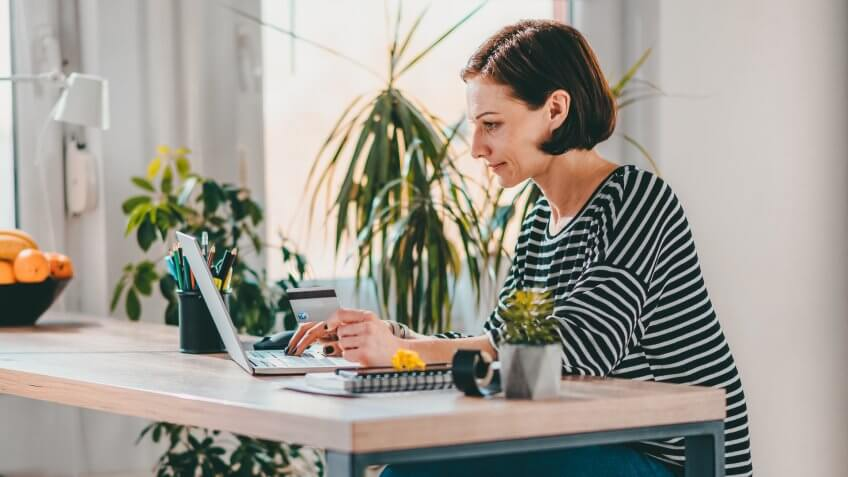 Woman using laptop and shopping online while holding credit card at the desk by the window.