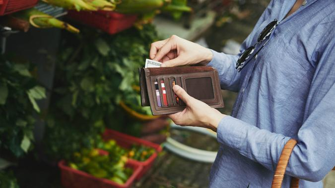 Woman taking money out of wallet to pay for the vegetables.