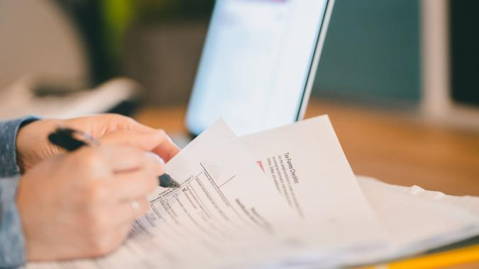 A woman scans through a W-9 forms as she does her taxes.