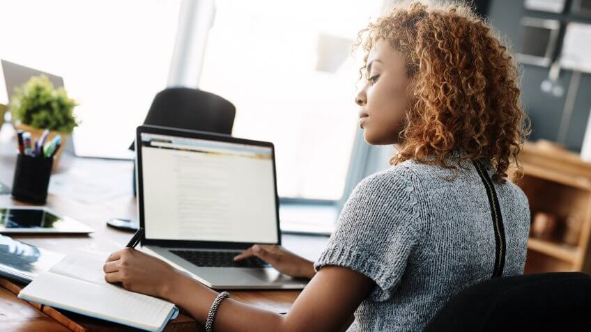 Shot of a young businesswoman working on a laptop in an office.