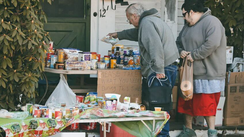 Mandatory Credit: Photo by Charles Krupa/AP/Shutterstock (10587538b)Two residents select items on a community table, filled with groceries for those in need, in Derry, N.