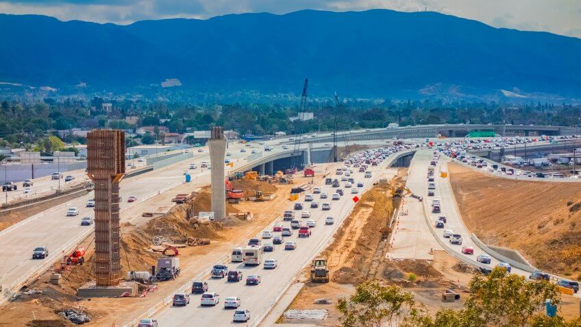Overpass construction and equipment with traffic on the 91 Freeway fills the foreground leading back to hills in background with clouds above, Riverside California.