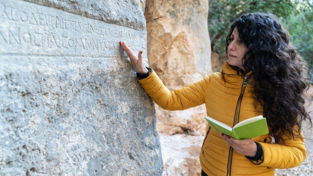 Female archaeologist standing by a stone antique stone structure and writing notes to notebook while examining ancient Latin script written on rock.