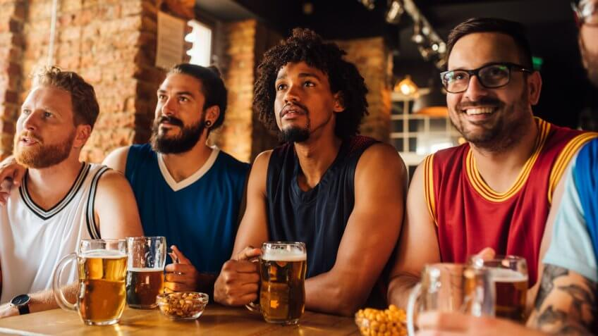 Multi - ethnic group of basketball fans watching a basketball game and drinking beer at the pub.