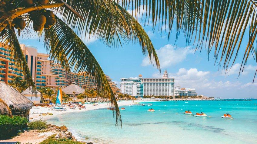 Cancun beach with hotels and plam tree in foreground.