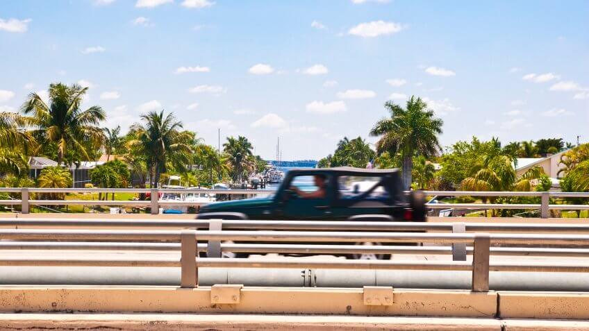 Car speeding over a canal bridge in southern Florida.