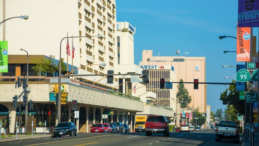 Fresno, United States - March 8, 2015: Downtown Fresno Street Scene, looking down Van Ness Avenue, with a Radisson Hotel, and several office buildings in the scene, and cars in the lower part of the view, and banners on the side of the street advertising Downtown Fresno.