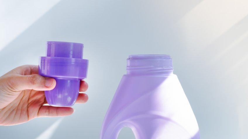 woman hand using liquid laundry softener detergent washing cloth.
