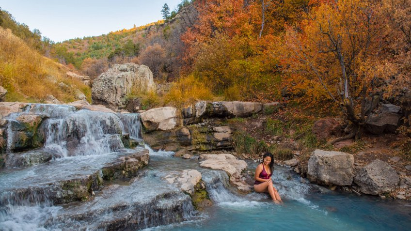 Woman relaxing at Fifth Water Hot Springs in Utah, USA during autumn.