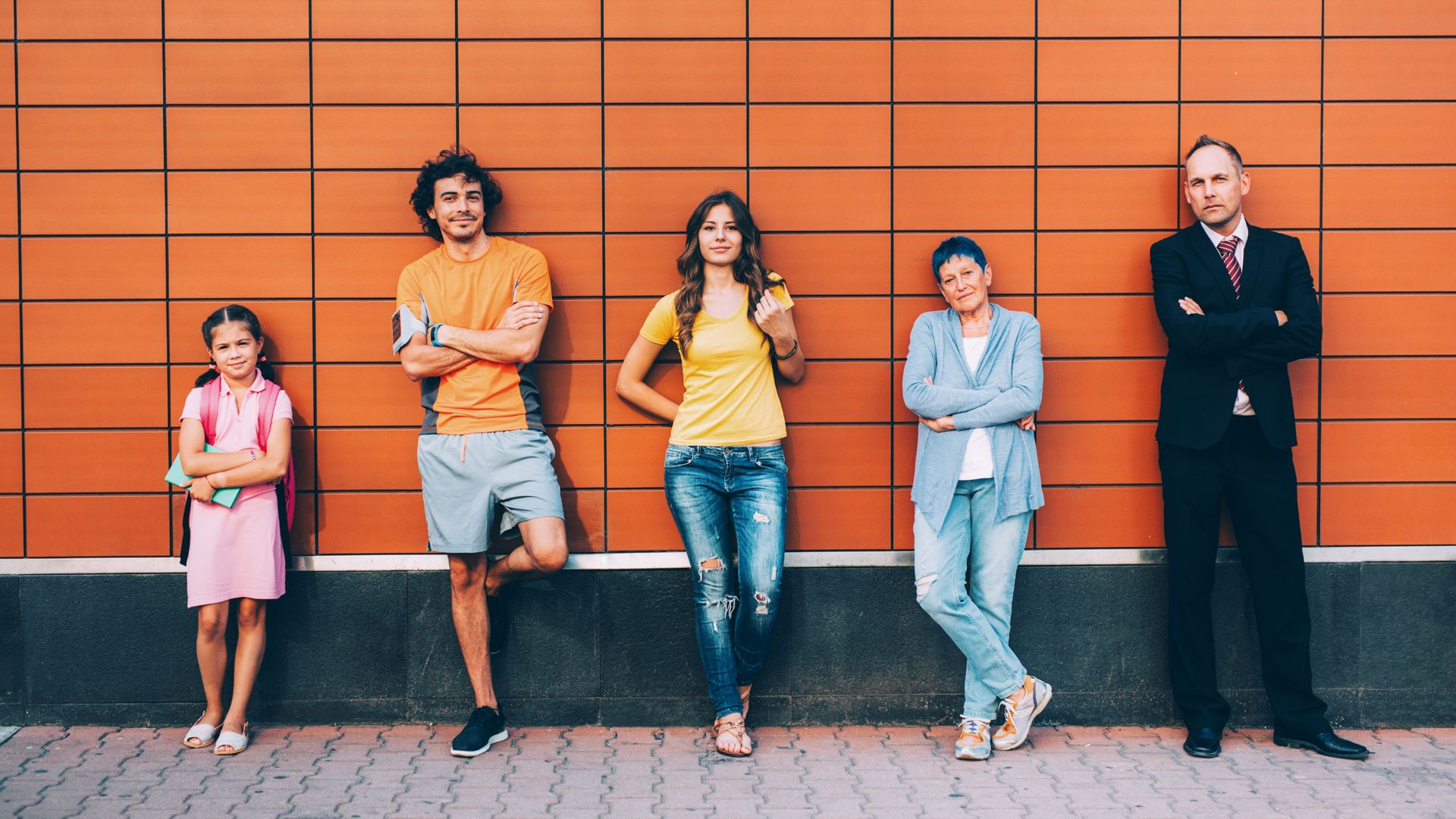 Five people at different ages standing agains a wall seperately.