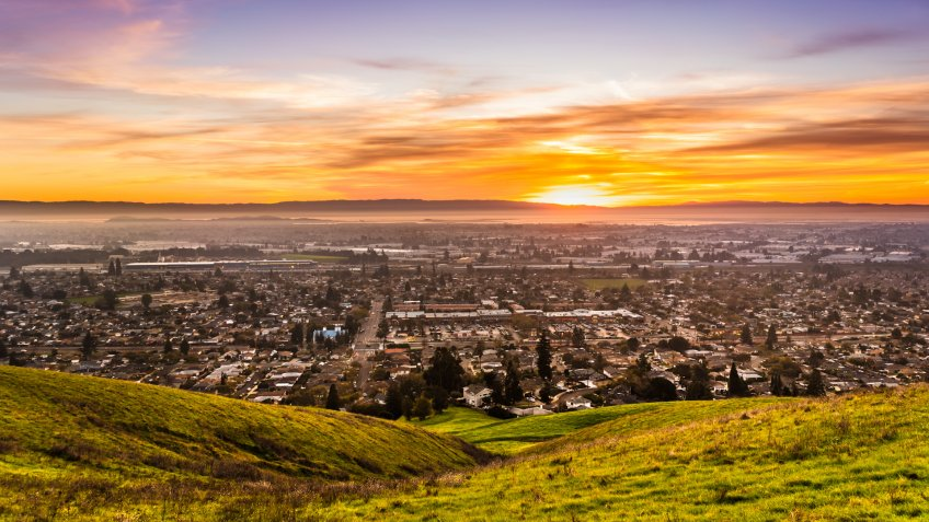 Sunset view of residential and industrial areas in East San Francisco Bay Area; green hills visible in the foreground; Hayward, California.