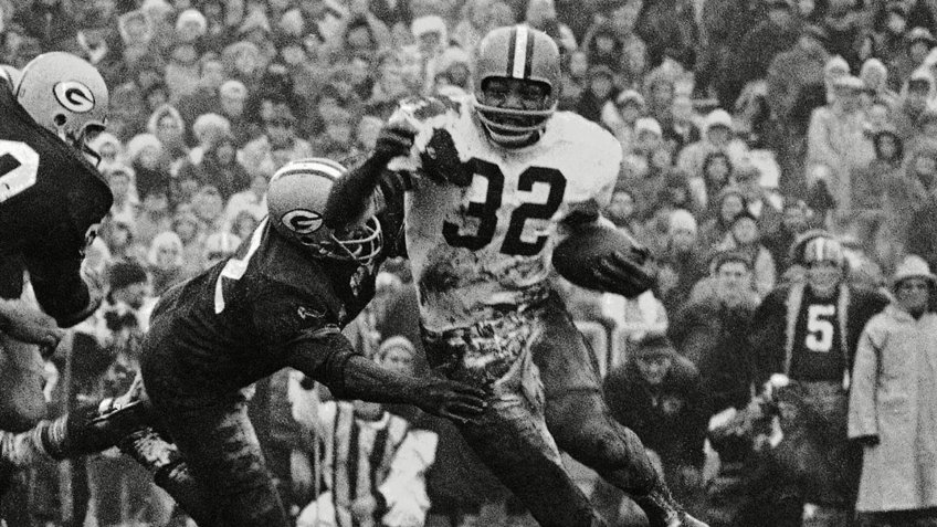 Cleveland Browns' Jim Brown (32) turns the corner as a Green Bay Packer defender swings with him during a football game in Green Bay, Wisc.