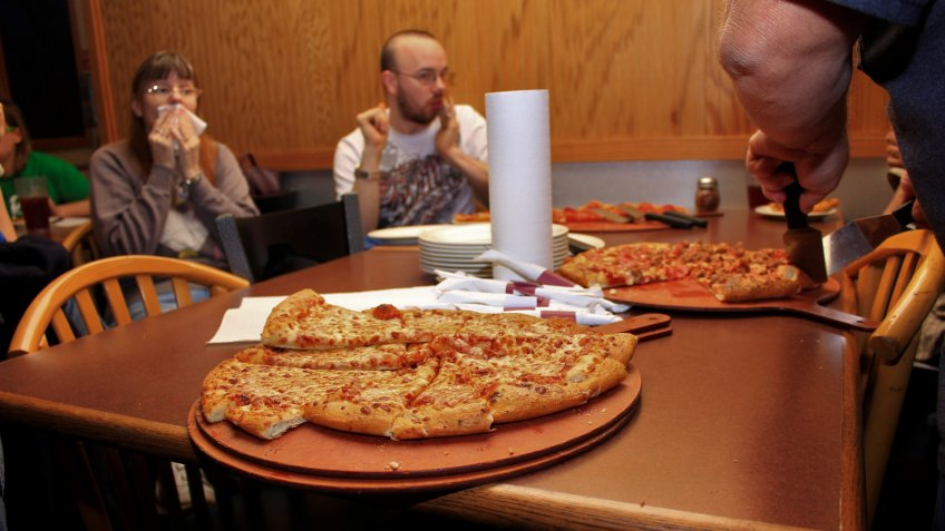 A shot of Pizza thats for supper on a table thats sliced on a plate thats ready to eat.