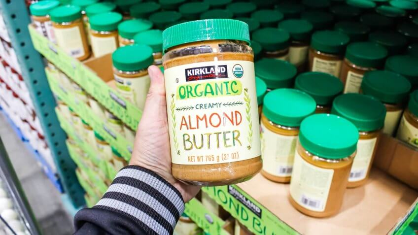Tustin, California/United States - 02/08/2020: A hand holds a jar of Kirkland Signature organic creamy almond butter on display at a local Costco.